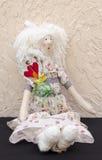 有一朵花的手工制造玩偶在他的在一件长的白色礼服si的传送带 库存照片