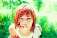 有一朵花的红发女孩在他的嘴 免版税库存图片