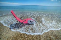 有一朵花的红色躺椅和海滩帽子在海滩 休息,夏天,幸福,放松大气  库存照片