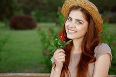 有一朵花的美丽的妇女在公园 免版税库存照片