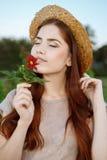 有一朵花的美丽的妇女在公园 免版税图库摄影