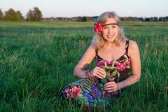 有一朵花的美丽的妇女在她的坐在领域的头发 图库摄影
