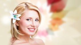 有一朵花的美丽的白肤金发的妇女在头发 图库摄影