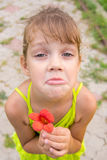 有一朵花的滑稽的女孩在她的手上蹲下了乞求看对框架的面孔 库存照片