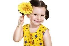有一朵黄色花的俏丽的女婴在她的手上 库存图片