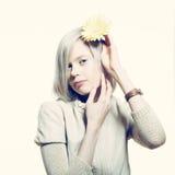 有一朵黄色花的奇怪的亭亭玉立的白肤金发的女孩在她的头发 免版税库存照片