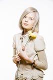 有一朵黄色花的奇怪的亭亭玉立的白肤金发的女孩 库存图片