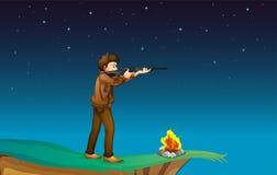 有一杆枪的一个男孩在与营火的峭壁 免版税库存照片
