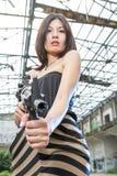有一杆枪的亚裔妇女在废墟 免版税库存照片