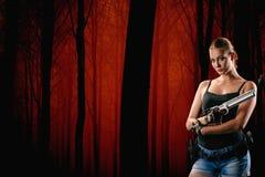 有一杆枪的军事妇女在黑背景 库存照片