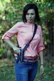 有一杆枪的女孩在他的手上 图库摄影
