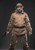 有一杆枪的战士在黑暗的背景 免版税库存照片