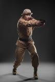 有一杆枪的战士在黑暗的背景 图库摄影