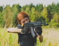 有一杆枪的红头发人女孩在他的手上 免版税库存图片