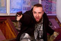 有一杆枪的有胡子的恐怖分子在一个被毁坏的风雨棚的子座 库存照片