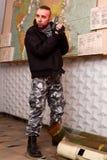 有一杆枪的恐怖分子在一个被毁坏的风雨棚的子座 库存照片