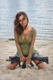 有一杆步枪的女孩在海滩 库存图片