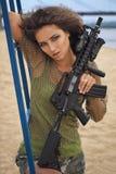 有一杆步枪的女孩在海滩 免版税库存照片