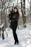 有一杆步枪的妇女在冬天森林里 库存照片