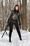 有一杆步枪的妇女在森林里 免版税库存照片