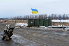 有一杆步枪的战士在检查站 乌克兰 免版税图库摄影