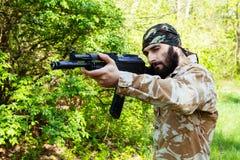 有一杆步枪的有胡子的战士在森林 免版税库存照片
