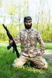 有一杆步枪的有胡子的战士在森林 免版税库存图片