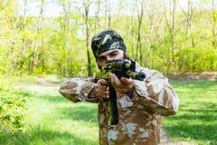 有一杆步枪的有胡子的战士在森林 库存图片