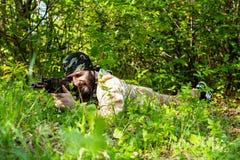 有一杆步枪的有胡子的战士在森林 图库摄影