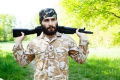 有一杆步枪的有胡子的战士在森林 免版税图库摄影