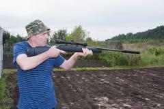 有一杆气动力学的枪的人 免版税库存照片