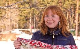 有一条五颜六色的围巾的快乐的女孩在他的手上 免版税库存照片