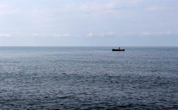 有一条偏僻的渔夫` s小船的蓝色海 库存照片