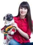 有一条哈巴狗狗的微笑的女孩在毛线衣 库存照片