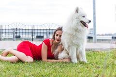 有一条大白色狗的女孩 免版税库存图片