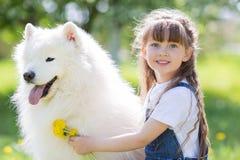 有一条大白色狗的小女孩在公园 免版税图库摄影