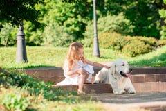 有一条大白色狗的小女孩在公园 白色礼服的一个美丽的五岁的女孩拥抱她喜爱的狗在wal一个的夏天期间 库存照片