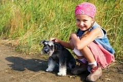 有一条她的狗的逗人喜爱的矮小的美国女孩步行的 免版税图库摄影