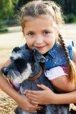 有一条她的狗的逗人喜爱的矮小的美国女孩步行的 库存照片
