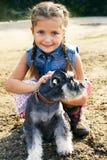 有一条她的狗的逗人喜爱的矮小的美国女孩步行的 图库摄影
