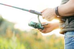 有一条实心挑料铁杆传染性的鱼的渔夫在河 免版税图库摄影