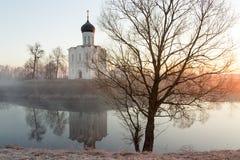 有一条小船的一个有薄雾的湖在教会前面在早期的春天在黎明 库存照片