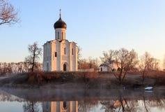 有一条小船的一个有薄雾的湖在教会前面在早期的春天在黎明 图库摄影