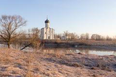 有一条小船的一个有薄雾的湖在教会前面在早期的春天在黎明 免版税图库摄影