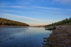 有一条小船的渔夫在日落的河Varzuga点燃 库存照片