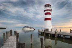 有一条小船的灯塔在日落 免版税库存照片