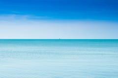 有一条小船的镇静蓝色海在无边地海 免版税库存照片