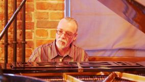 有一条尾巴的一个灰发的人在他的顶头佩带的玻璃热心地和周道地弹在爵士乐的钢琴 影视素材