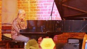 有一条尾巴的灰发的人在他的有弹在爵士乐酒吧的玻璃的头钢琴 影视素材