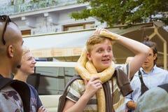 有一条巨大的黄色蟒蛇蛇的红发男孩 免版税库存照片